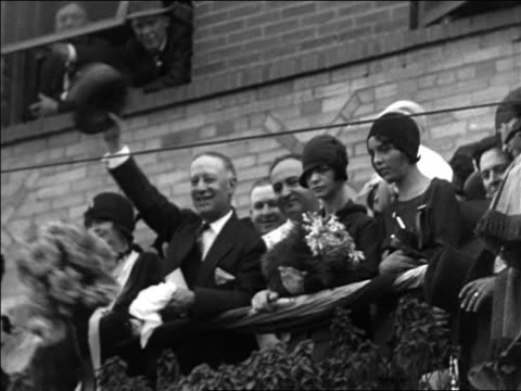 b/w 1928 low angle al smith standing on balcony waving hat / documentary - 1928 stock-videos und b-roll-filmmaterial
