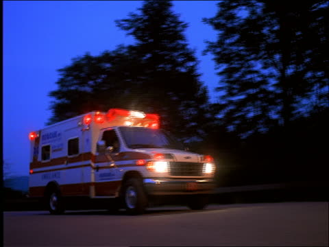 low angle PAN ambulance with flashing lights drives past camera at dusk