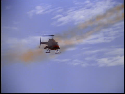 low angle Army helicopter flying in blue sky / firing off guns / Rio de Janeiro, Brazil