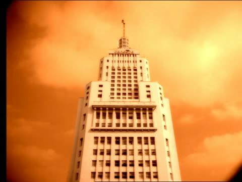 sepia low angle art deco skyscraper with flag atop under clouds - tonad bild bildbanksvideor och videomaterial från bakom kulisserna