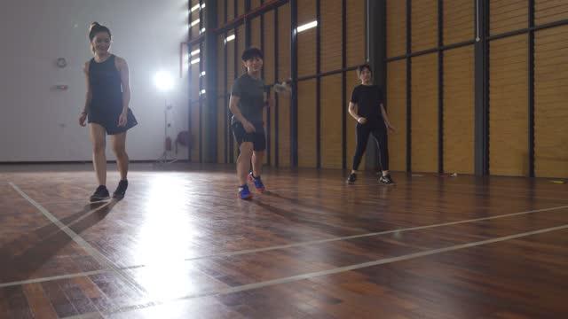 vídeos y material grabado en eventos de stock de bajo ángulo asiático chino jugadores de bádminton practicando en el entrenamiento de resistencia pista de bádminton - miembro parte del cuerpo