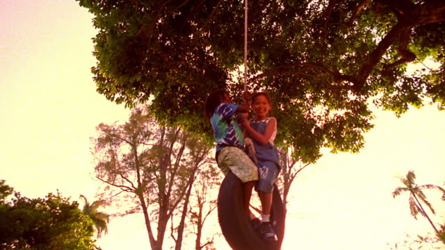 low angle asian girl + black boy swinging on tire swing - tyre swing stock videos & royalty-free footage