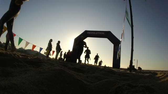 low angle, at sunrise, triathletes have finished swim and head from water up beach. sunrise - triatleta video stock e b–roll