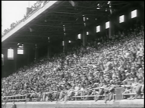 B/W 1933 low angle audience standing up in bleachers at track and field event / Philadelphia