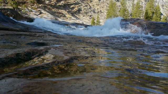 ms low angle pov, backlit cascading water, granite slope & trees in background, green reflections in water, tuolumne river, yosemite national park, california - granite stock videos & royalty-free footage
