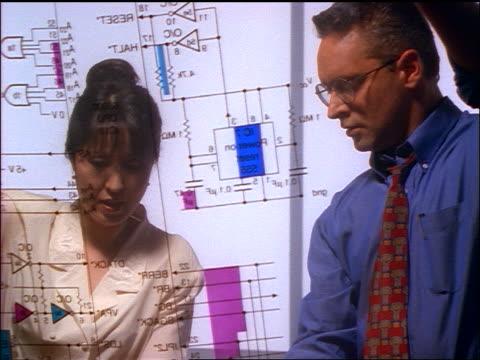vidéos et rushes de low angle beneath light table of businessman + asian businesswoman looking at schematic transparency - équipement informatique