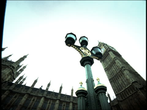 vídeos de stock e filmes b-roll de high contrast low angle big ben + parliament with ornate street light in foreground / london, england - ano 2000