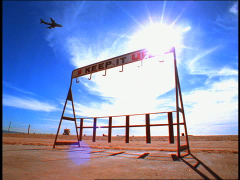 """vídeos de stock, filmes e b-roll de low angle bike rack with """"keep it up"""" sign on beach with airplane flying overhead / venice beach (flash frame) - superexposto"""