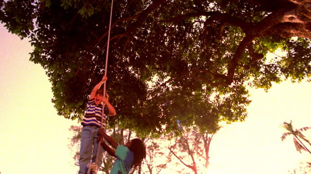 low angle black boy + boy swinging on tire swing - tyre swing stock videos & royalty-free footage