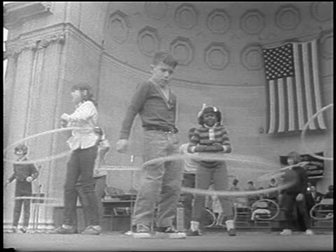 b/w 1967 low angle black + caucasian children on outdoor stage in plastic hoop contest / nyc / newsreel - plastic hoop stock videos & royalty-free footage