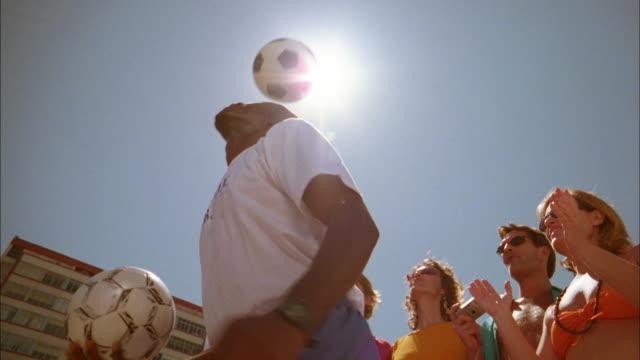 vídeos de stock e filmes b-roll de low angle black man heading soccer ball against sun in background / tourists taking photos - copacabana
