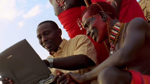low angle ms black man showing laptop computer to masai tribesmen / kenya - indigenous culture stock videos & royalty-free footage
