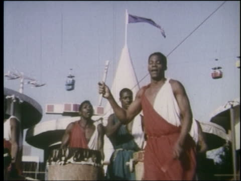 1964 low angle pan black men in native african dress playing drums dancing / ny world's fair - 1964年点の映像素材/bロール