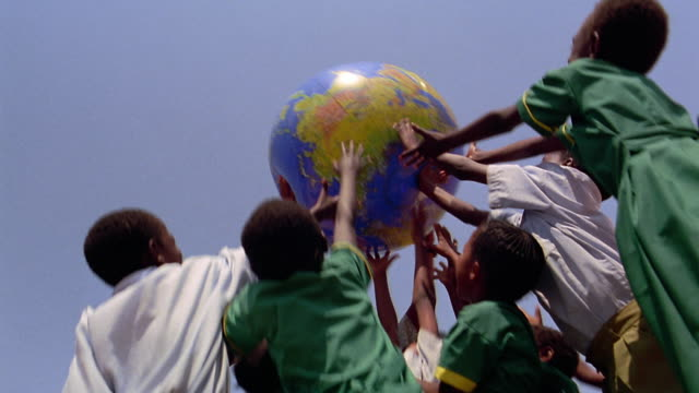 low angle ms black schoolchildren + teacher playing with inflatable globe outdoors / kenya - inflatable stock videos and b-roll footage