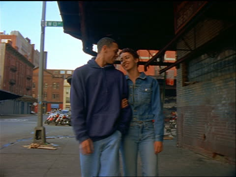 low angle Black teen couple smiling + walking arm-in-arm on sidewalk / Meat Packing District, NYC