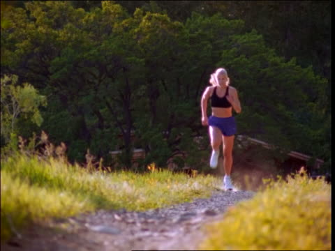 stockvideo's en b-roll-footage met low angle blonde woman jogging on path towards camera - jogster