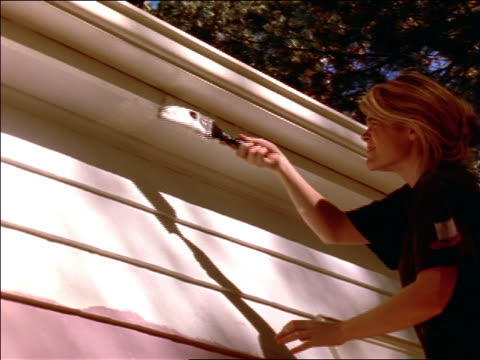 low angle blonde woman on ladder painting house exterior - ladder stock videos and b-roll footage