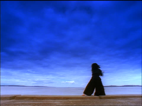 vídeos de stock e filmes b-roll de low angle blue woman in black samurai outfit using sword by ocean - samurai