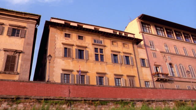 low angle pan boat point of view buildings on shore of arno river / florence, italy - florenz italien stock-videos und b-roll-filmmaterial