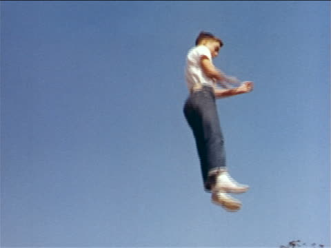 1962 low angle boy in jeans bouncing high in air on unseen trampoline / industrial