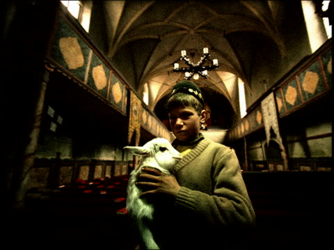 grainy low angle ms boy in native dress holds baby goat inside church / sibiu, transylvania / flash frames - manipolazione di colore video stock e b–roll