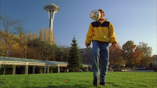 low angle boy kicking soccer ball with space needle in background / seattle - one teenage boy only stock videos and b-roll footage