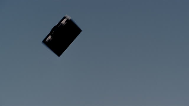 low angle briefcase flying through air with blue sky in background - aktentasche stock-videos und b-roll-filmmaterial