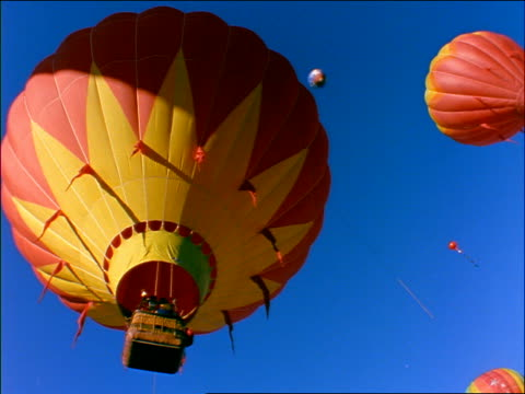 low angle pan brightly colored hot air balloons flying in clear blue sky / snowmass, colorado - whatif点の映像素材/bロール
