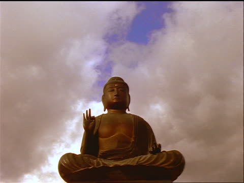 low angle Buddha statue with time lapse clouds in background