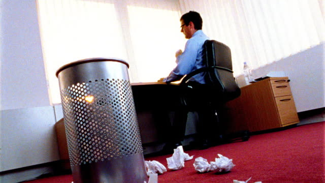 canted low angle businessman at desk throws crumpled paper onto floor littered with papers by trashcan in foreground - wastepaper bin stock videos & royalty-free footage