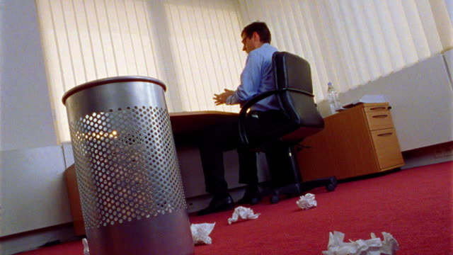 canted low angle businessman at desk throws crumpled paper onto floor littered with papers by trashcan in foreground - crumpled paper stock videos and b-roll footage