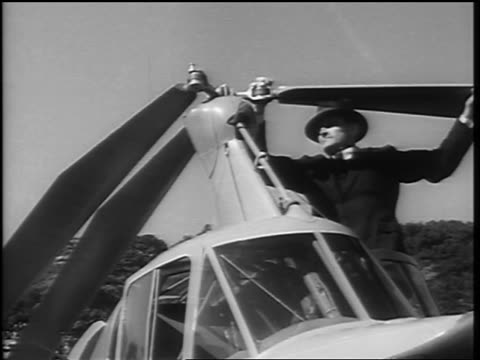 B/W 1936 low angle businessman folding back rotor blades of autogiro / Washington DC