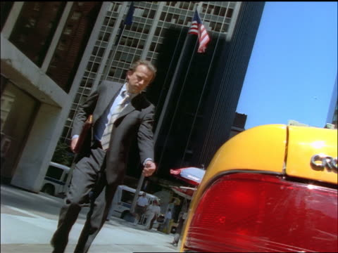 low angle businessman getting into taxicab on NYC street