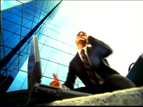 vídeos de stock e filmes b-roll de overexposed low angle businessman on cell phone sitting by laptop stands up, jumps + raises fist by bldg - super exposto