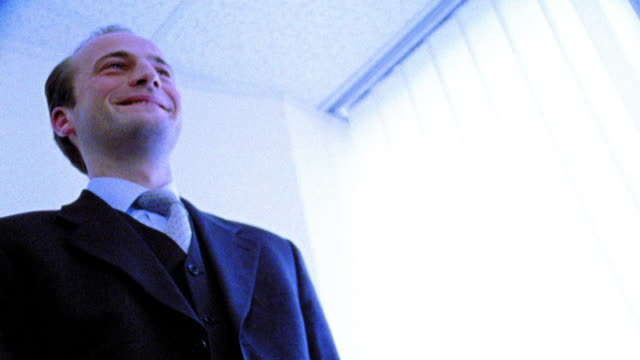 BLUE OVEREXPOSED low angle MS businessman smiling + shaking hand of person out of frame