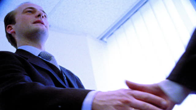 BLUE OVEREXPOSED low angle MS businessman smiling + shaking hand of woman out of frame
