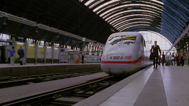 low angle businessman walking towards camera / high speed train pulling out of station / Frankfurt, Germany