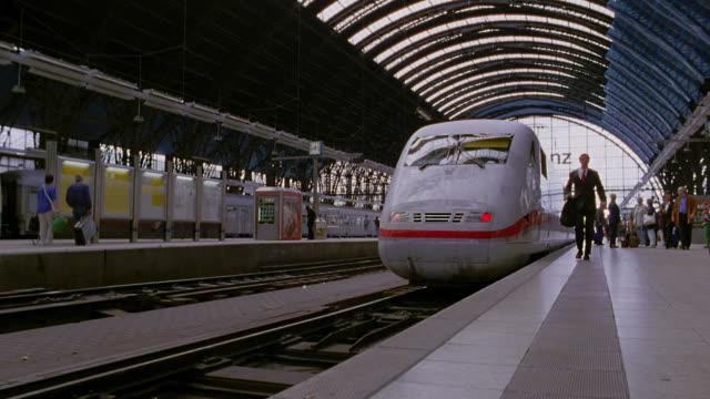 vídeos y material grabado en eventos de stock de low angle businessman walking towards camera / high speed train pulling out of station / frankfurt, germany - estación de tren