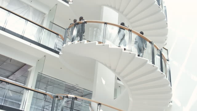 low angle, businesspeople walk down spiral staircase - staircase stock-videos und b-roll-filmmaterial