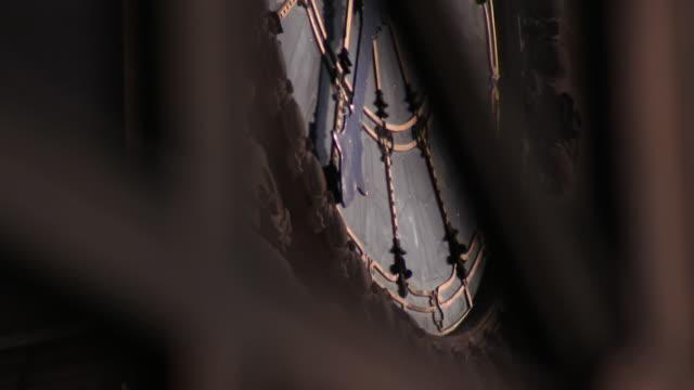 Low angle camera tilt up over clock face inside Paris Gare de Lyon station