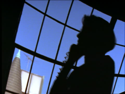 low angle canted silhouette of businesswoman talking on phone in front of window - landline phone stock videos and b-roll footage