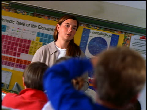 low angle canted teacher standing before rear view of class, calling on students as they raise hands - menschlicher arm stock-videos und b-roll-filmmaterial