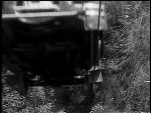 B/W 1932 low angle car driving on stretched cables over camera / Barlow, OR