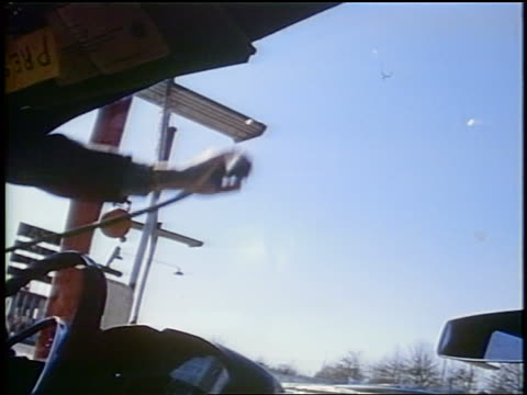 1958 low angle car point of view man's hand spraying cleaner on windshield / steering wheel in foreground / newsreel - cleaner stock videos and b-roll footage