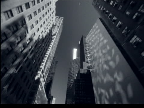 B/W low angle car point of view of tall buildings on city street / NYC