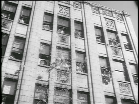 vidéos et rushes de b/w 1952 low angle car point of view people throw confetti ticker tape from building windows during parade / news - 1952