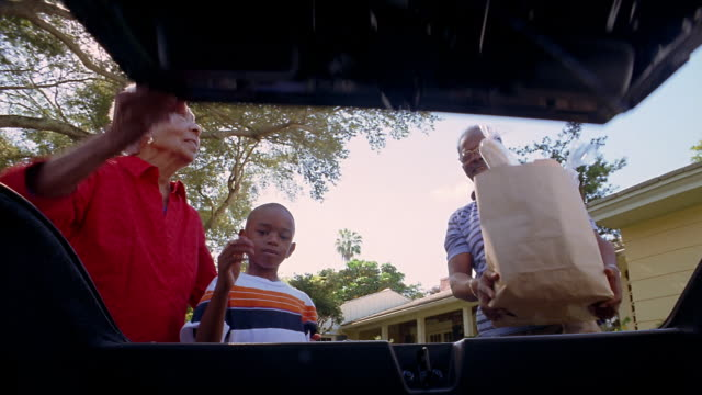 Low angle car trunk point of view trunk opening / boy and grandparents putting groceries in trunk of car/ trunk closing