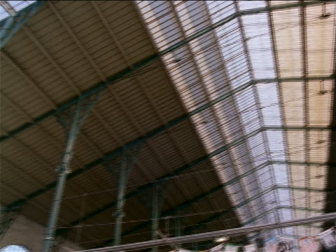 low angle PAN ceiling of Gare de Lyon / tilt down from crowd to point of view toward bullet train + platform / Paris, France