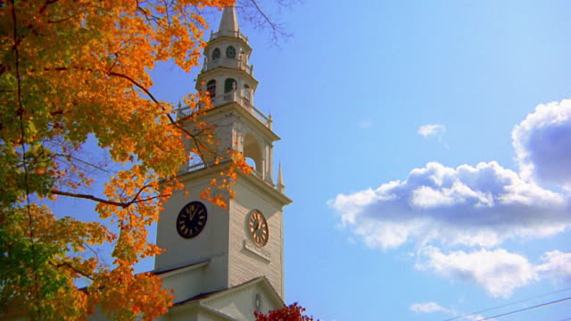 Low angle clock tower and branches of trees with orange leaves / New England