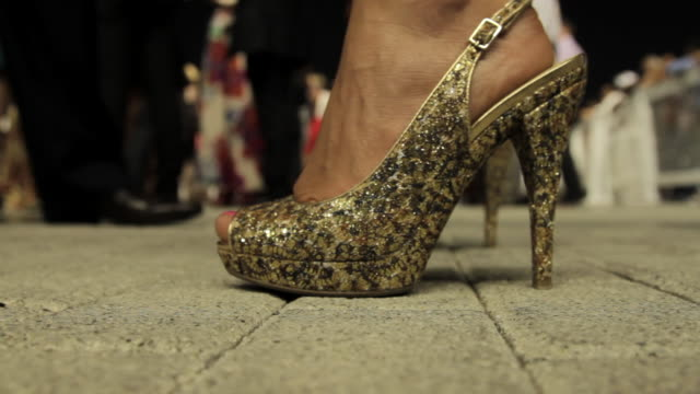 Low angle close shot of a woman wearing a pair of glittery gold high heels.
